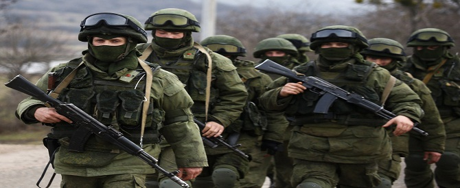 Armed men, believed to be Russian servicemen, march outside an Ukrainian military base in the village of Perevalnoye