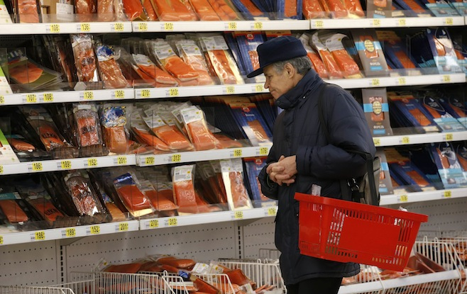 Customer stands in front of shelves at the fish department of a hypermarket of French grocery retailer Auchan in Moscow