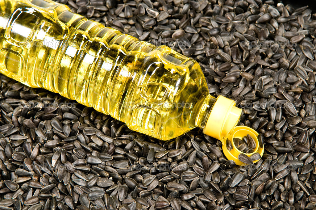 Plastic bottle with sunflower-seed oil against sunflower seeds.