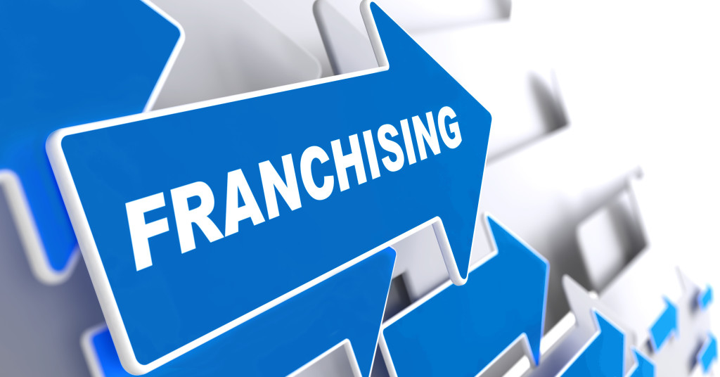 """Franchising - Business Background. Blue Arrow with """"Franchising"""" Slogan on a Grey Background. 3D Render."""